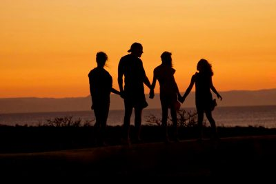 Silhouette Of Four Family Members Holding Hands With Sunset Backdrop. Happy Family.