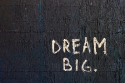 Dream Big Written In White On Black Wall.