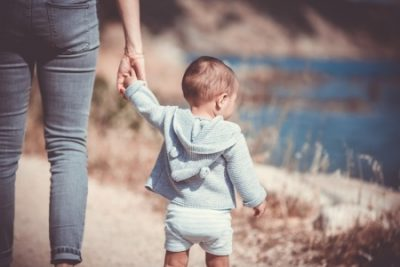 Small Child Walking Hand In Hand With Mother.