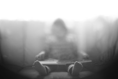 Blurry Image Of Child Sitting On Couch.