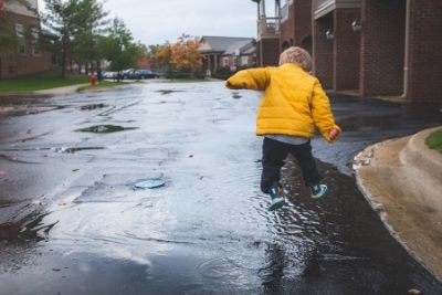 Little Boy Jumping In Puddle. Boy Wearing Yellow Raincoat.