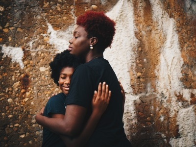 African Mother And Daughter Hugging In Front Of Wall. Happy Family.