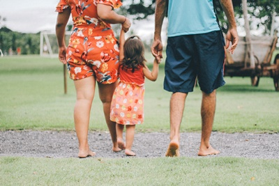 Family walk. Child holing hands with parents.