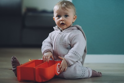 Cute Toddler Playing On The Floor.