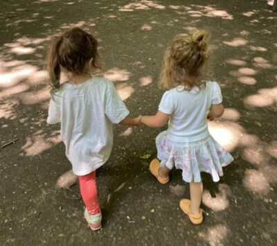 Small Girls Holding Hands In Park.
